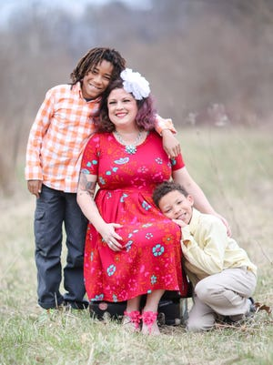 Michelle stands with her two boys, Justice and Lorenzo, who were both adopted from Flint.