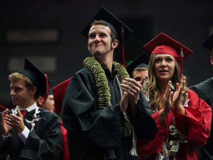 Hurricane High graduates stand to applaud the friends and family who helped them graduate during the Hurricane High School graduation ceremony at the Burns Arena on Wednesday, May 21, 2014.