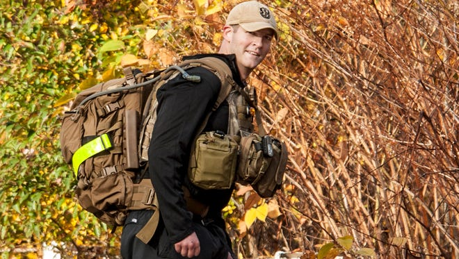 """Army Capt. Justin Fitch marches to work Oct. 23, 2013, as part of his training for the campaign """"Carry the Fallen,"""" to raise money and awareness for veterans and families who deal with post-traumatic stress disorder and suicidal tendencies."""