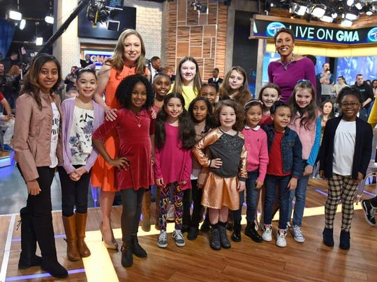 Tiana Sirmans, in red, stands in front of Chelsea Clinton during a picture on the Good Morning America set.