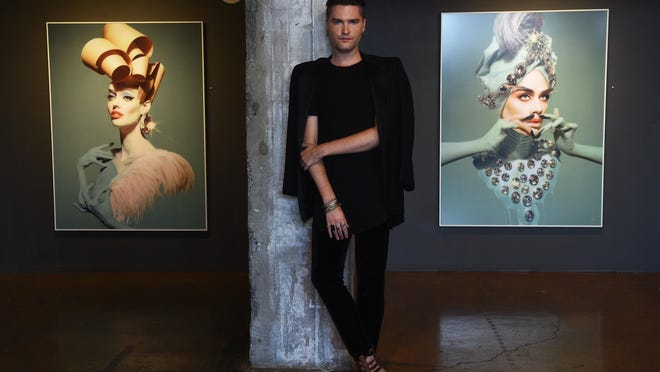 Artist Franz Szony poses for a portrait in front of some of his work at the Sierra Arts Gallery in Reno on July 1, 2015.