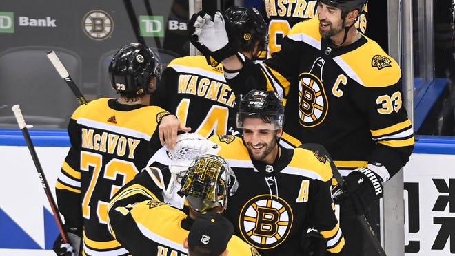 Bruins defenseman Zdeno Chara (33) and centerPatrice Bergeron (37) celebrate with teammates after eliminating the Carolina Hurricanes from the first round of the Eastern Conference playoffs in Toronto on Wednesday.
