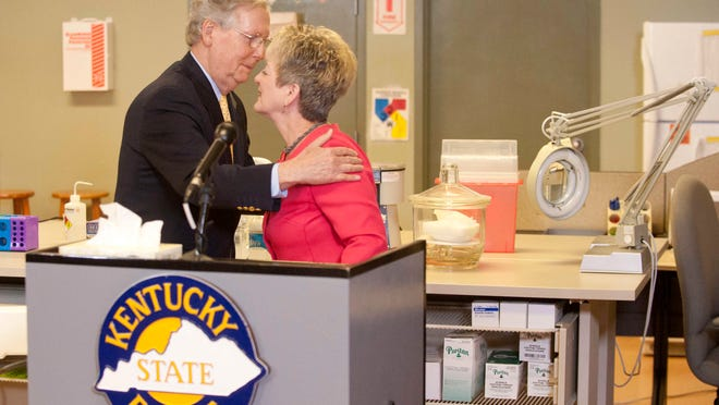U.S. Sen. Mitch McConnell who was at the Ky State Police crime lab in Louisville to stump for renewed funding for the Debbie Smith Act hugs Smith, a rape victim for whom the act is named. The law provides states with federal funding to help speed up the backlog of rape kit testing done by the labs. 12 August 2014