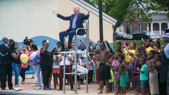 Former Vice President Joe Biden sits in the lifeguard chair and cheers along with the crowd as they reveal the renaming of the pool facility being dedicated in his honor to the Joseph R. Biden Jr. Aquatic Center.