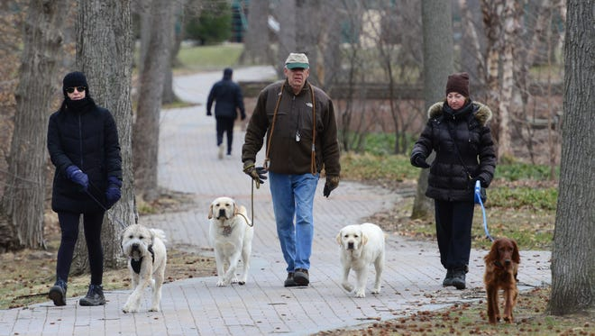 From left, Chris Messing, of Maywood, with her dog Hank; Randy Kremer, of Paramus, with his dogs, Jaeger and Lilly; and Elena Zubov, of Paramus, with her dog Agatha, walk along a trail at Van Saun County Park in Paramus on Tuesday morning March 20, 2018.