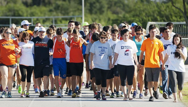 The family, right, and friends of Estero High School coach Jeff Sommer, honored his passing by taking a lap on the school's track during a memorial gathering for Sommer at Estero High School on Sunday. Sommer died while coaching at the FHSAA state championships in Jacksonville