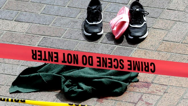 Clothing is strewn on the sidewalk at a scene where pedestrians were hit by a motorist in Portland, Friday, May 25, 2018. Police say three women have been injured in a hit-and-run crash near Portland State University.