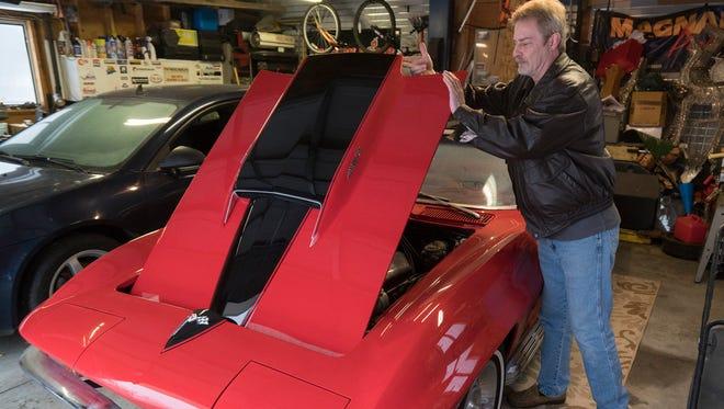 Chris Velfling lifts the hood of his 1967 Corvette.