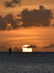 A paddleboarder admires the sunset from the Dungca's