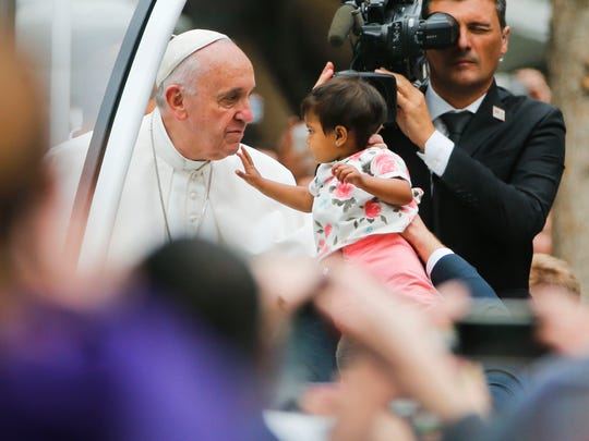 An unidentified child, who was carried from the crowd, touches Pope Francis' face during a parade on his way to celebrate Sunday Mass on the Benjamin Franklin Parkway in Philadelphia on Sunday.