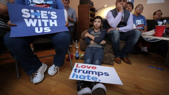 Abigail Holguin, 11, pays attention to the Presidential Debate between Hillary Clinton and Donald Trump Monday during the El Paso County Democrats' debate watch party Monday. Assuming the next President is a two-term president, Holguin will be of voting age. Casey Antonio Williams is at right and Marie Mier, left.