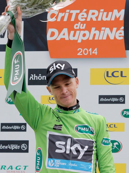 Team Sky's Christopher Froome celebrates with his green jersey on the podium after the last stage of the 66th Dauphine cycling race, in Courchevel, French Alps, Sunday, June 15, 2014. (AP Photo/Laurent Cipriani)