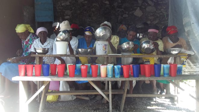 Guests at Pen ek Pwason soup kitchen in Borgne, Haiti put some food in containers to save for later.
