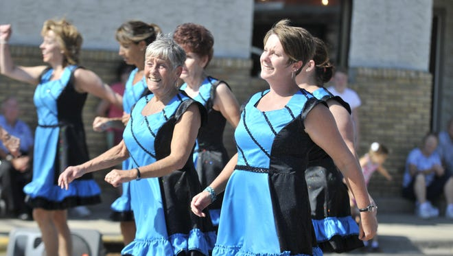Wendy Olson, center, and her daughter Christin Johnson, right, dance with the Granite City Cloggers at the Millstream Arts Festival Sunday in St. Joseph.