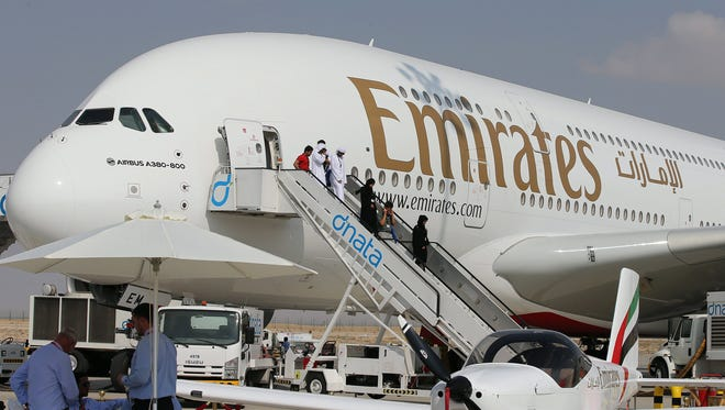 Visitors depart from an Airbus A 380 owned by Emirates airlines after inspecting the airplane at the exhibition of the Dubai Air show 2013 at Dubai Al Maktoum international airport in the United Arab Emirates, Nov. 18, 2013.
