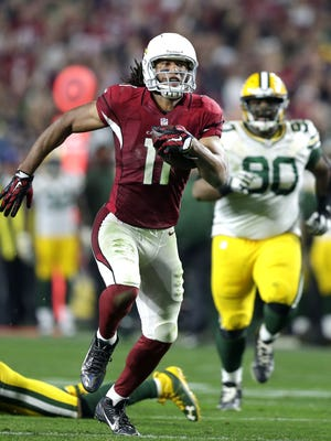 Arizona Cardinals receiver Larry Fitzgerald breaks away for 75-yard pass play in overtime to set the Cardinal's offense up in the red zone Saturday night at the University of Phoenix Stadium  in Glendale, Arizona.