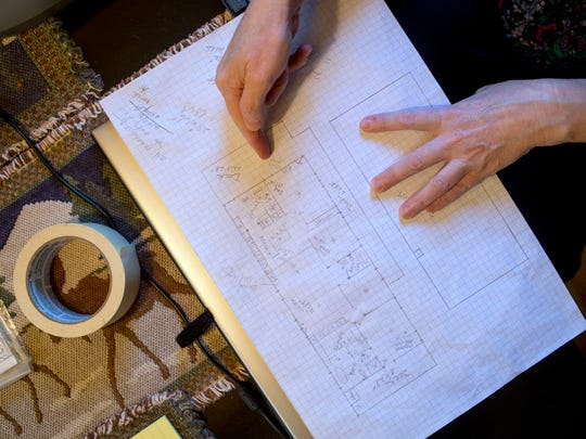 "Lisa McCarter shows the blueprint of the home they are building after the Gatlinburg fires destroyed the original structure. ""The house will be different, but the view out our windows, the plants in the yard, the layout of the grounds will be familiar,"" McCarter said."