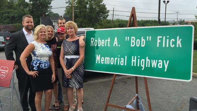 "Members of Robert A. ""Bob"" Flick's family celebrate after a road sign is dedicated in honor of the Hebron grocer."