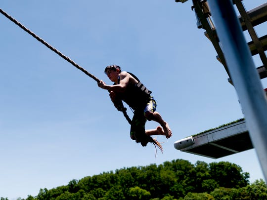 Brady Nichol jumps into the water with a rope at the