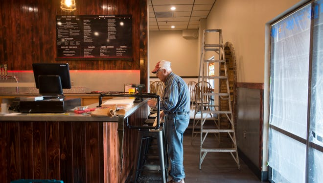 Donn DeCoursey works to hang artwork at Panhandler's Pizza on Saturday, March 24, 2018. The Campus West staple is re-opening with new ownership on College Avenue.