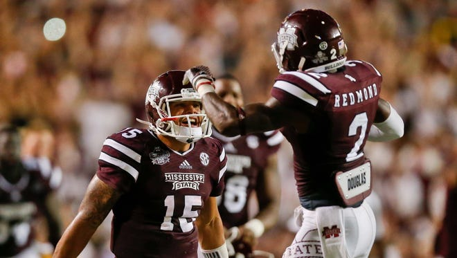 Sep 20, 2014; Baton Rouge, LA, USA; Mississippi State Bulldogs quarterback Dak Prescott (15) celebrates with defensive back Will Redmond (2) following a win over the against the LSU Tigers in a game at Tiger Stadium. Mississippi State defeated LSU 34-29. Mandatory Credit: Derick E. Hingle-USA TODAY Sports