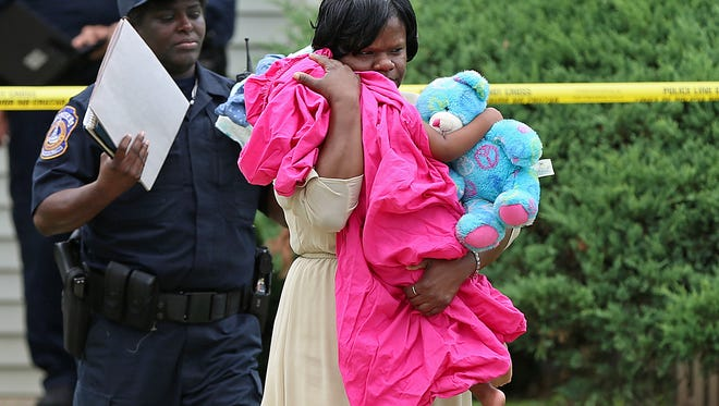 An Indianapolis Police Department victim's assistant carries an unharmed infant girl from an apartment on Admar Court near 46th Street and Binford Boulevard where three people were found fatally shot Friday morning, July 22, 2016.