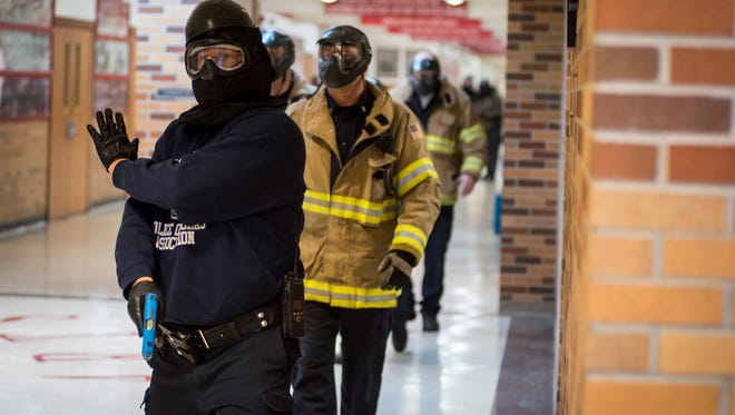 First responders, escorted by law enforcement officers, walk through the hallway of Port Huron High School during a hostile event simulation Saturday, April 14. First responders are escorted by police officers as they search for injuries and casualties.A law enforcement officer guides first responders through Port Huron High School while they search for injuries and casualties during a hostile event simulation Saturday, April 14.