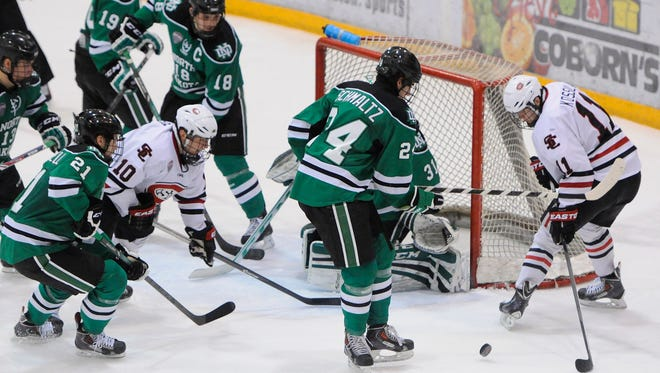 St. Cloud State's Kalle Kossila (11) and Ryan Papa (10) try to get control of the puck in front of the North Dakota goal during a game last season at the Herb Brooks National Hockey Center in St. Cloud.
