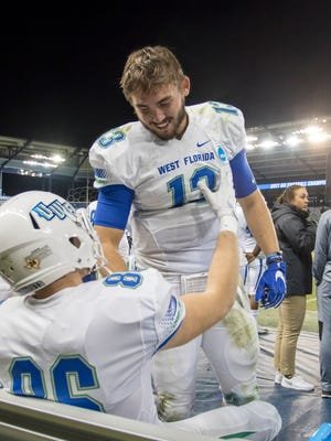 QB Mike Beaudry (13) consoles teammate Josh Lindsey (86) as time runs out in the University of West Florida 37-27 loss to Texas A&M - Commerce in the NCAA Division II National Championship football game at Children's Mercy Park in Kansas City, Kansas on Saturday, December 16, 2017.