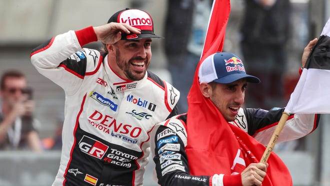 Swiss driver Sebastien Buemi (R) from the #8 Toyota Gazoo Racing car waves to fans together with teammate Fernando Alonso (left) after winning the classic 24 hours of Le Mans race on June 17, 2018