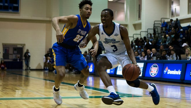 Texas A&M Corpus Christi's  Joseph Kilgore dribbles the ball past St. Mary's Demarco Enoch during their game Friday, Dec. 14, 2017, at Dugan Wellness Center.