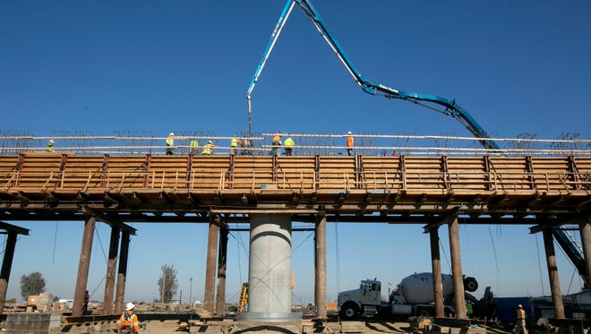 Workers pour concrete on to one of the elevated sections of the high-speed rail that will cross over the San Joaquin River, near Fresno.
