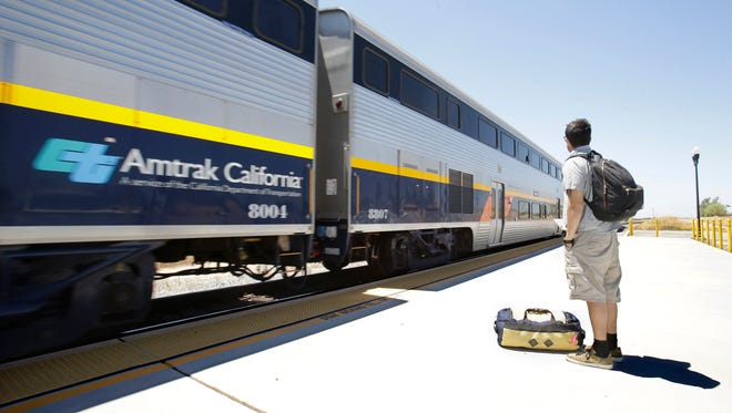 A passenger waits to board an Amtrak California train in Madera, Calif., on July 17, 2013.