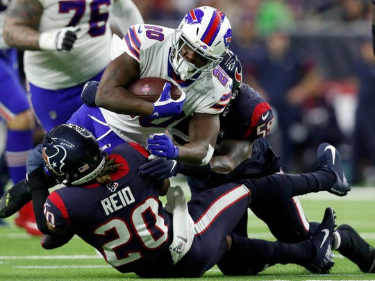 HOUSTON, TEXAS - JANUARY 04: Running back Frank Gore #20 of the Buffalo Bills is tackled by strong safety Justin Reid #20 of the Houston Texans during the AFC Wild Card Playoff game at NRG Stadium on January 04, 2020 in Houston, Texas. (Photo by Tim Warner/Getty Images)
