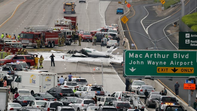 Emergency responders gather around the crash of a Cessna 310 aircraft on Interstate 405, just short of a runway at John Wayne Airport in Costa Mesa.