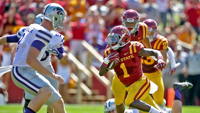 Iowa State's #1 Jarvis West, right, made a sharp cut to the center of the field to elude Kansas State defenders as West scored his team's second touchdown on punt return during football game at Jack Trice Stadium in Ames on Saturday Sept. 6, 2014.