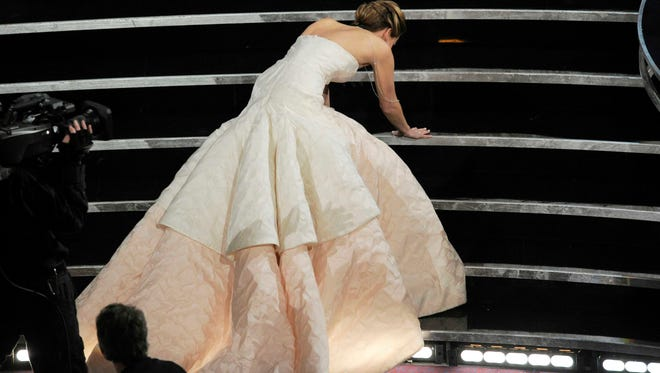 Jennifer Lawrence stumbles as she walks to the stage to accept best actress for 'Silver Linings Playbook' at the 2013 Oscars.