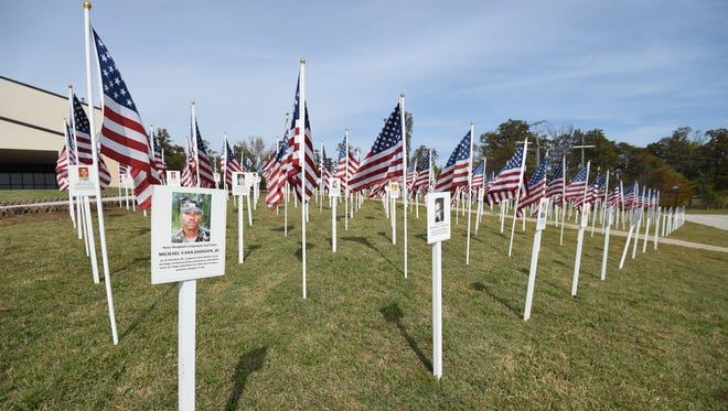 Flags honoring Arkansas veterans who have died since the September 11 attacks flutter in the wind Tuesday in front of Twin Lakes Baptist. The flags are part of the Arkansas Fallen Heroes Traveling Memorial. Each flag has the photograph of an Arkansas veteran who has died while serving since September 11, 2001 and a brief summary of how the veteran died. The memorial will be on display through Sunday.