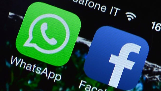 This file picture taken on Feb. 20, 2014 in Rome shows the Facebook and WhatsApp applications' icons displayed on a smartphone.