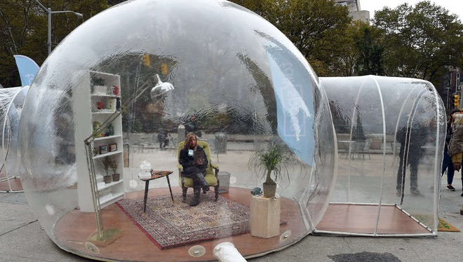 Talkspace therapist Christy Paul texts a patient  from a plastic bubble set up in New York November 5, 2014, during the kickoff of the Talkspace #PopupTherapy showcase.