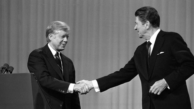 In this Oct. 28, 1980, photo, President Jimmy Carter shakes hands with GOP presidential candidate Ronald Reagan after debating in the Cleveland Music Hall in Cleveland. The fall debates are always a big part of any presidential campaign. But with many 2016 voters underwhelmed by both Hillary Clinton and Donald Trump, this year's debates could well be more influential than usual.