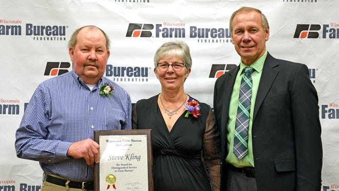 The Steve Kling family has long tradition of service to Wisconsin Farm Bureau Federation. WFBF President Jim Holte (right) presents Steve Kling with the Distinguished Service to Farm Bureau Award.