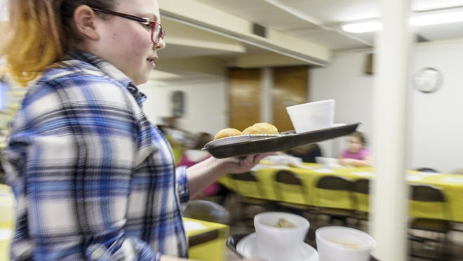 Dine with Freedom, hosted by Freedom for Youth, was held at the First Congregational Church in Mitchellville May 4. Freedom for Youth kids prepared and served a dinner for attendees. Megan Burge of Freedom for Youth takes two dinners to the tables.