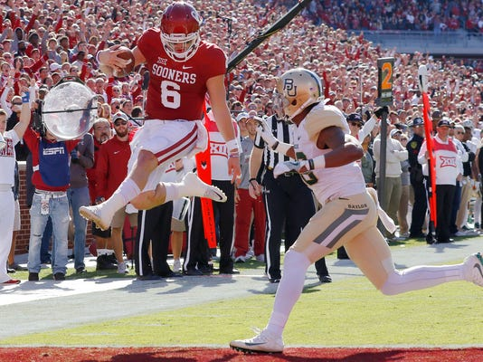 FILE - In this Nov. 12, 2016, file photo, Oklahoma quarterback Baker Mayfield (6) runs in for a touchdown ahead of Baylor safety Davion Hall (2) during the first half of a NCAA college football game in Norman, Okla. Third-ranked Oklahoma is streaking into the Big 12 opener at Baylor on Saturday. The 3-0 Sooners have a nation's-best 13 straight wins, and a 16-game winning streak in conference play. (AP Photo/Alonzo Adams, File)
