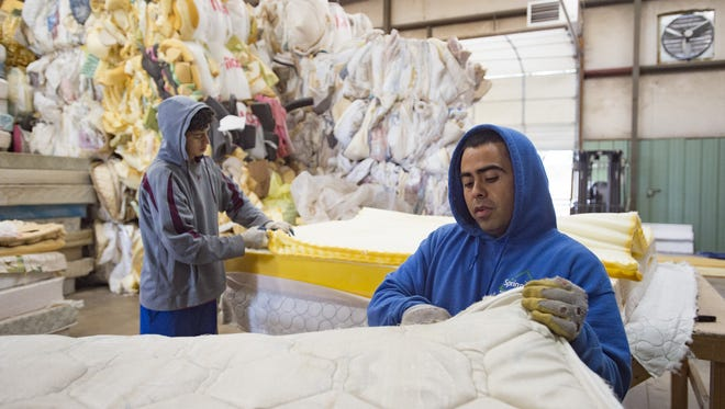 Roberto Valdez removes the outer cloth layer from a mattress at Spring Back Mattress Recycling in Fort Collins on Thursday, September 28, 2017. All mattresses are stripped for materials and sent to other locations for repurposing.