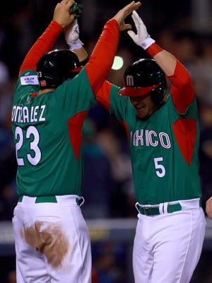 Adrian Gonzalez, left, and Brandon Laird celebrate Laird's fifth inning home run against Venezuela on Sunday night.