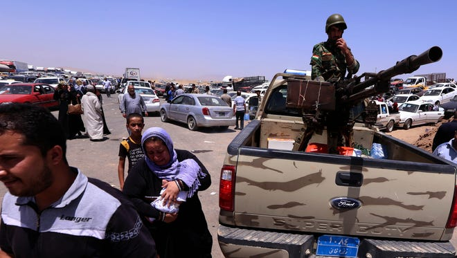 Iraqi families fleeing violence in northern Nineveh province gather at a Kurdish checkpoint in Aski Kalak, west of Arbil, in the autonomous Kurdistan region on Tuesday.