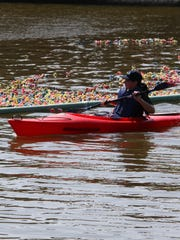 A kayaker watches the duck race at the 2014 Brockport Arts Festival.