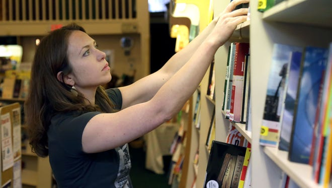 Llalan Fowler, the manager of Main Street Books, sorts titles at the store in the Carousel District of downtown Mansfield.