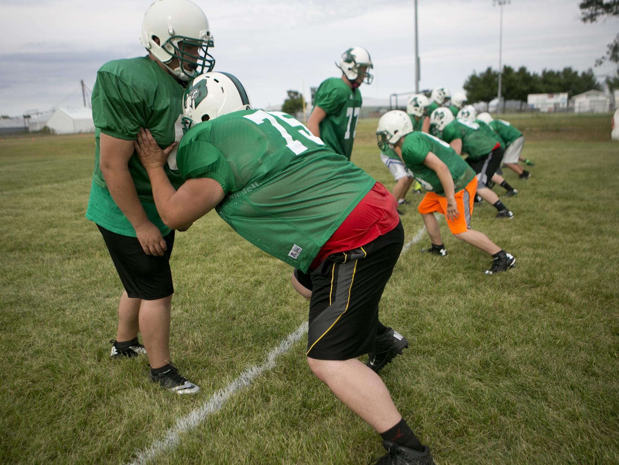 Linemen go through drills during Almond-Bancroft football practice on Thursday.